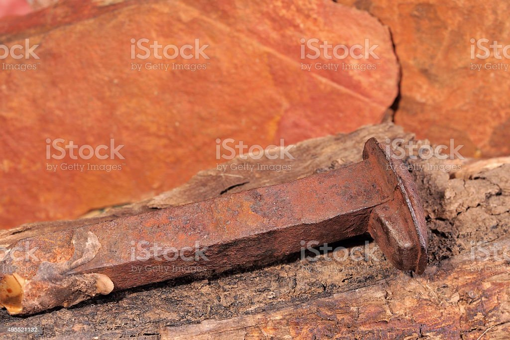 Rusted nail of the Ghan railway on timber stock photo