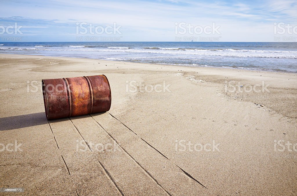 Rusted old barrel on sand beach stock photo