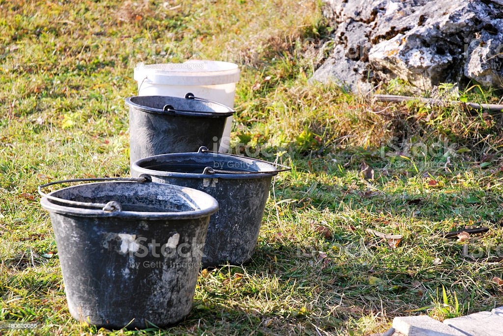 Rusted old Buckets on green field stock photo