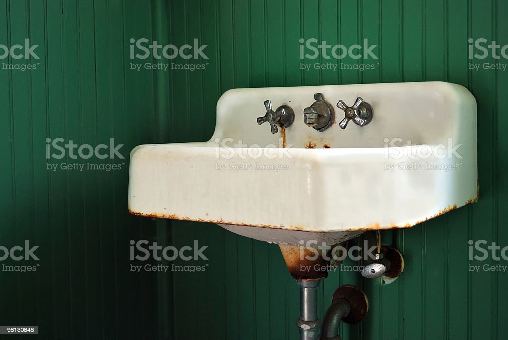 Rusted Old Sink and Fixtures on Green Panel Wall royalty-free stock photo