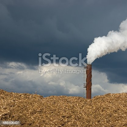 Large smoke steam, rusted smokestack, polluting chimney closeup, beige woodchips pile stack, dark blue cloudscape sky, detailed copy space