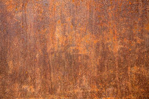 Photograph of a rusty steel door with peeling paint.