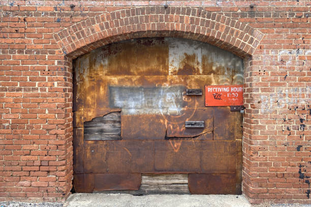 rusted warehouse delivery receiving bay door red brick building alley stock photo