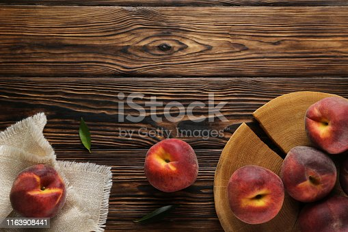 Bunch of ripe organic peaches in pile on textured table background. Local produce harvest heap on vintage style countertop. Clean eating concept. Top view, close up, copy space for text.
