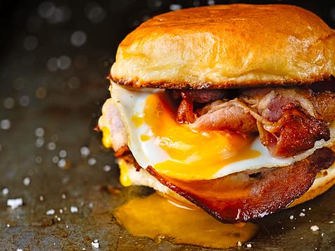 close up of rustic bacon egg breakfast sandwich bun