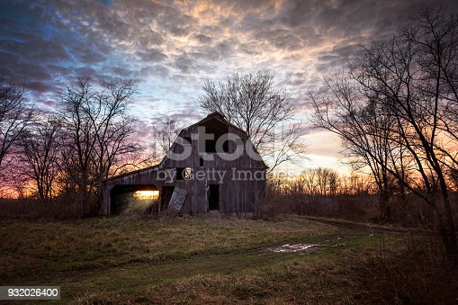An old rustic barn in the country at sunset.