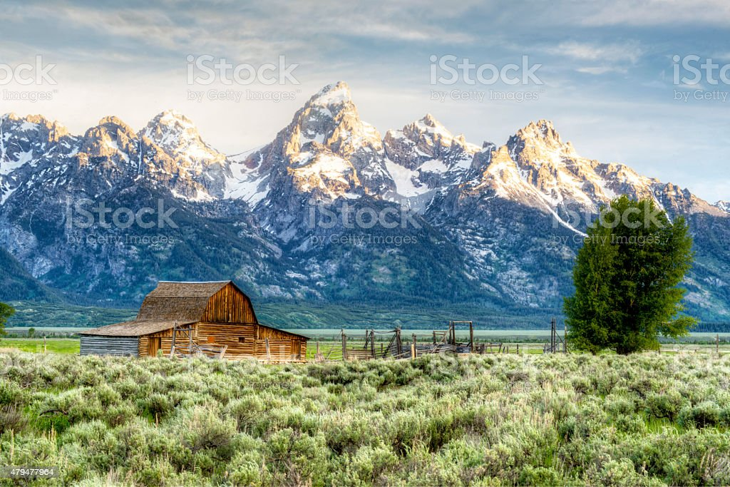 Rustic barn beneath snow capped mountains. stock photo