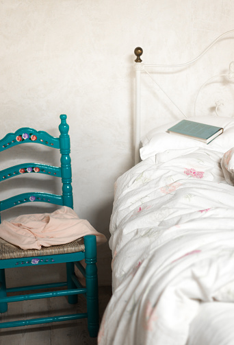 Rustic Bedroom with Blue Chair, Unmade Bed