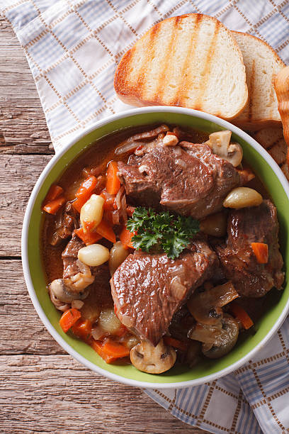 Rustic Beef Bourguignon in a bowl on a table close-up Rustic Beef Bourguignon in a bowl on a table close-up. vertical view from above beef bourguignon stock pictures, royalty-free photos & images