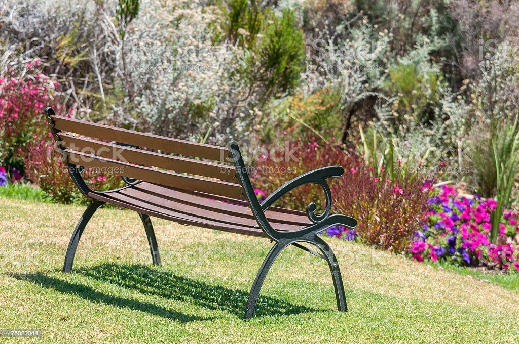 Rustic bench between flowers stock photo