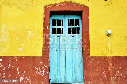 Mexicans like vivid colors for their houses, and doors. As it ages, its rustic look gives more character to it. In this picture, the blue door, gives a nice contrast to its yellow building.