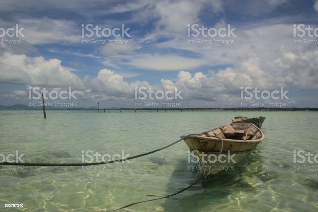 Rustic boat tied to shore in tropics stock photo