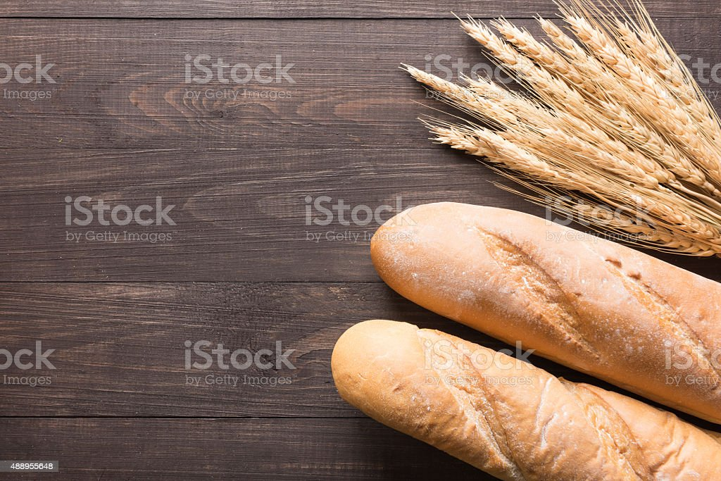 Rustic bread or baguette and wheat ears on wooden background stock photo