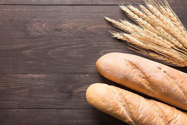Rustique baguette et pain et le blé oreilles sur fond en bois - Photo
