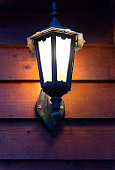 Rustic brown lamp attached outside a house on white wall