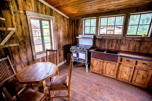 Old fashioned cabin interior in the kitchen area with details from the outside as well thanks to HDR.  Cabin is situated on a hillside high in an alpine mountainous area and was built by pioneers and restored many years later.  It has a wooden floor and an old fashioned gas stove