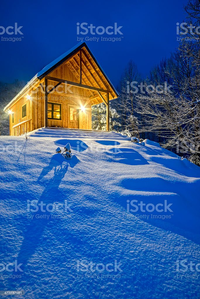 A rustic cabin on top of a snowy mountain royalty-free stock photo