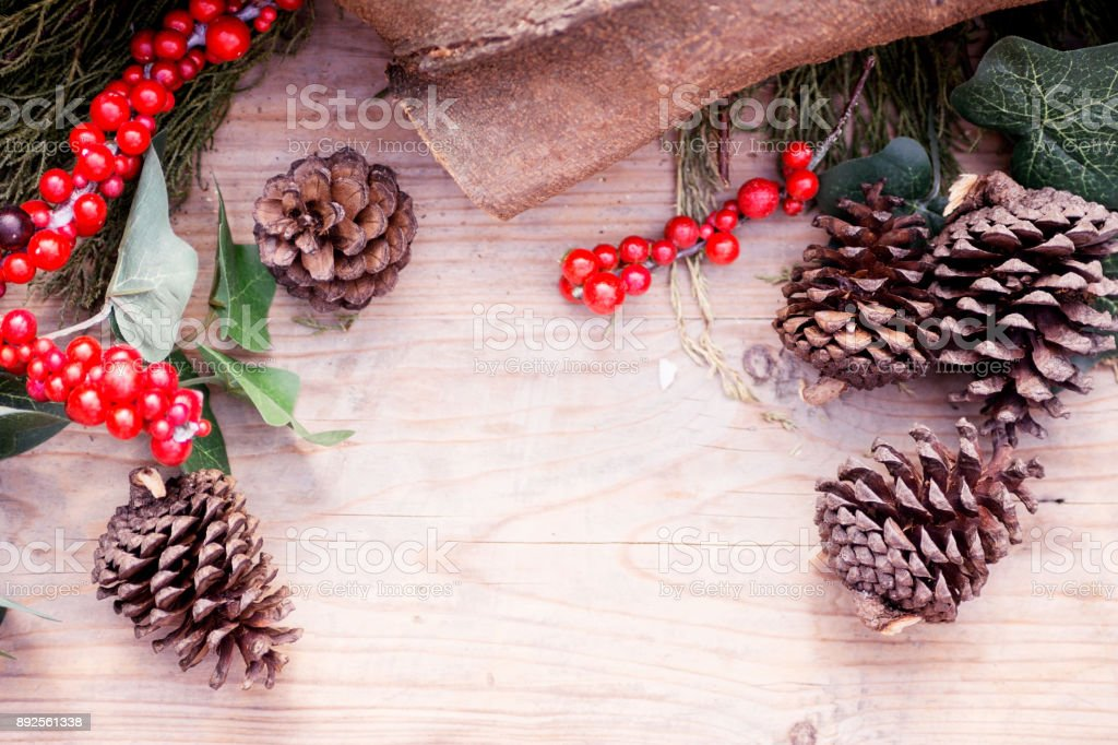 rustic christmas background: cypress branch, fir-cone and red berries on old wooden table. Chalet, country style. New year stock photo