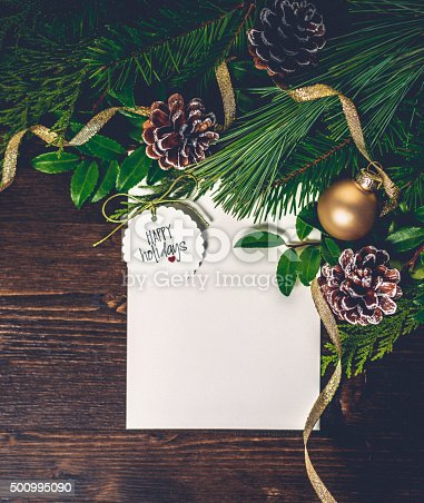 istock Rustic Christmas evergreen background with baubles and holiday message 500995090