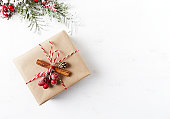 istock Rustic Christmas gift box with Christmas decorations on white wooden background. Flatlay. Copy space 1026534856