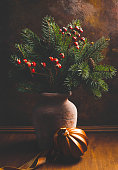 Rustic ceramic craft jug with a Christmas bouquet of fir and red berries.