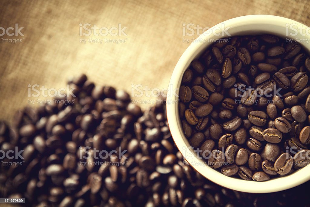 Fresh coffee beans on display on a brown burlap sack. Horizontal with...