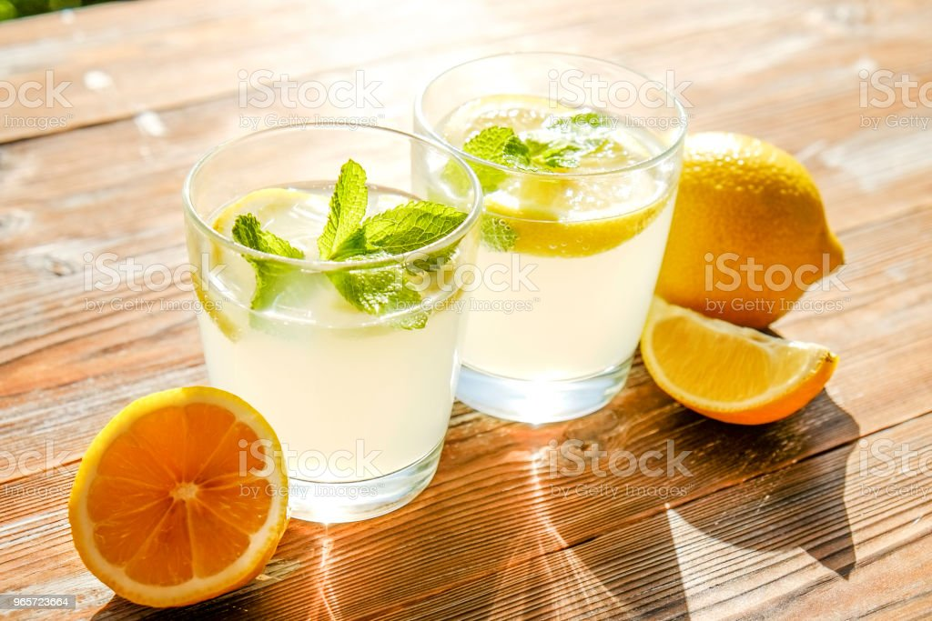 Rustic composition with freshly squeezed homemade cold lemonade in bottle and glasses with condensation droplets. - Royalty-free Bottle Stock Photo