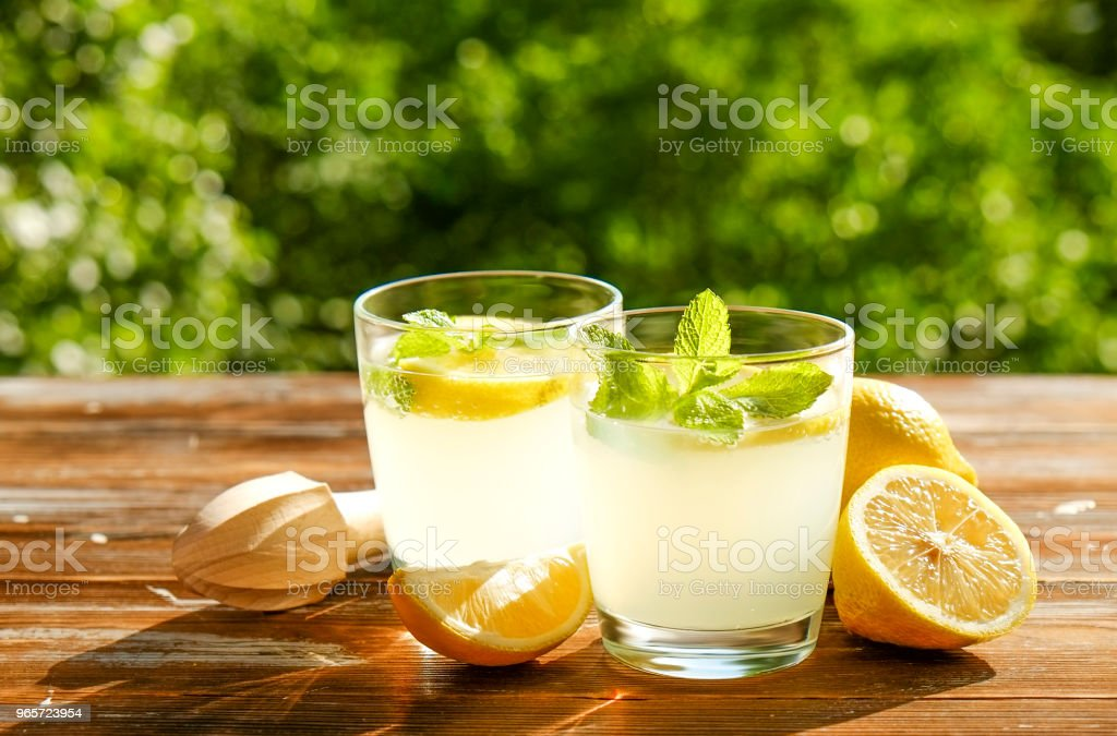 Rustic composition with freshly squeezed homemade cold lemonade in bottle and glasses with condensation droplets. - Стоковые фото Большой кувшин роялти-фри
