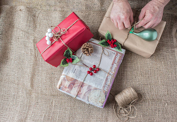 rustic country christmas style wrapped presents on burlap background very rustic country christmas image with man's hands wrapping christmas gift with brown paper and tying with baler twine with another gift wrapped in news paper with ginger bread story on it lying on a burlap background wrapping stock pictures, royalty-free photos & images