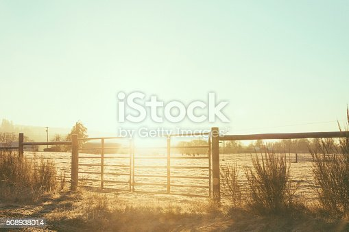 Country fence surrounding a cow pasture in a rural landscape.