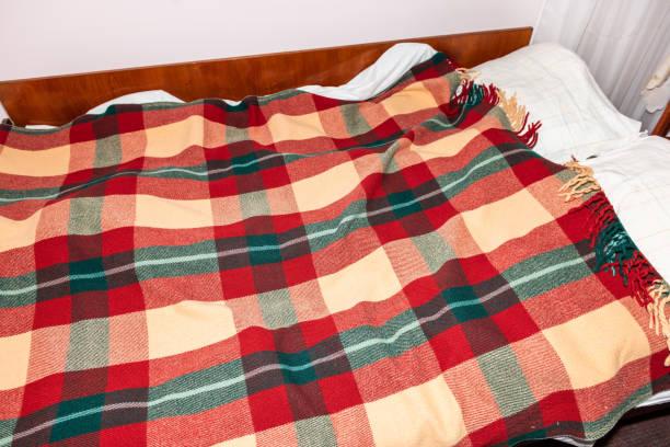 rustikale dacha landhaus haus oder haus hütte schlafzimmer mit futon-matratzenbett-kissen und machte bettwäsche wohnkomöpfen beschwämter wolle warme decke - bett landhausstil stock-fotos und bilder