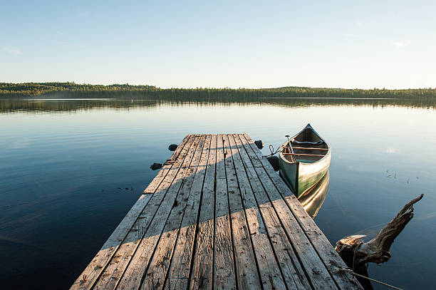 rustic dock with canoe at sunset in northern maine - nord foto e immagini stock