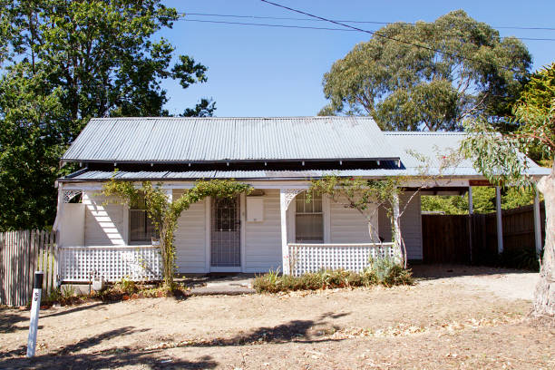 Rustic double fronted bungalow in Victoria State - Australia Melbourne, Australia: March 23, 2018: A typical detached double fronted bungalow home with a corrugated roof, white picket fence and verandah in Daylesford - Australia. run down stock pictures, royalty-free photos & images