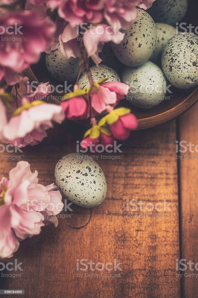 Rustic Easter still life. Speckled eggs, blossoms in rustic bowl. royalty-free stock photo