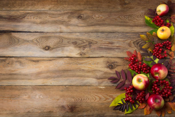 Rustic fall background with red leaves and apples stock photo