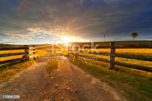 Gravel path onto rural property under golden sunset.