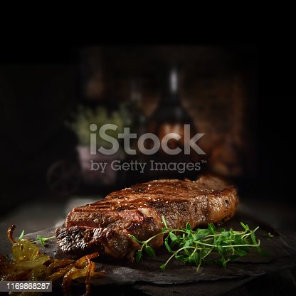 Succulent Farmhouse Rustic Rump Steak with thyme garnish shot against a dark background with wood burner. The perfect image for your bistro or restaurant menu cover art. Copy space.