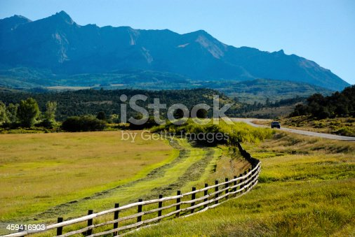 Rustic fence and highway below Mount Sneffels near Ridgway Colorado showing pastures and beginnings of cutting hay.