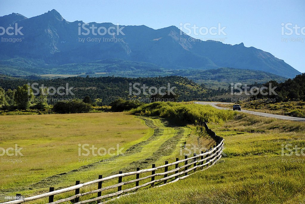 Rustic fence and highway below Mount Sneffels near Ridgway Colorado stock photo