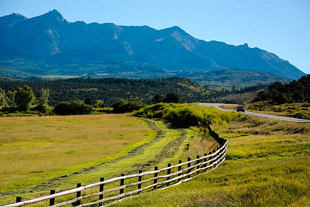 rustic fence and highway below mount sneffels near ridgway colorado - palisade boundary stock photos and pictures