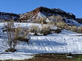 Rustic fence and new green grass and melting snow below South Mesa in Rockville Utah near Zion National Park Utah