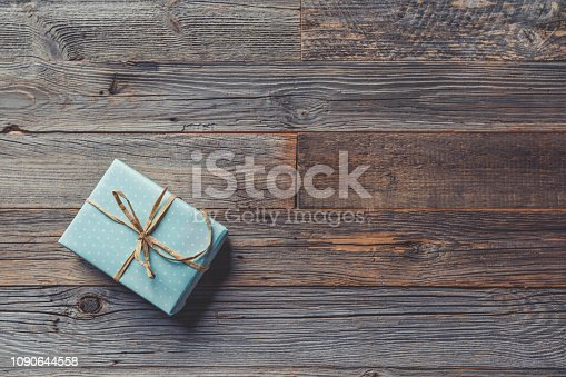 Rustic gift box on a wooden table. Shot from above tied with a bow. Copy space