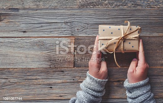 Rustic gift box on a wooden table. Shot from above tied with a bow. A woman is holding the gift in her hands. Copy space.