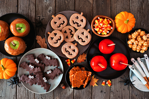 Rustic Halloween treat table scene over a dark wood background. Top view. Variety of candied apples, cookies, candy and sweets.