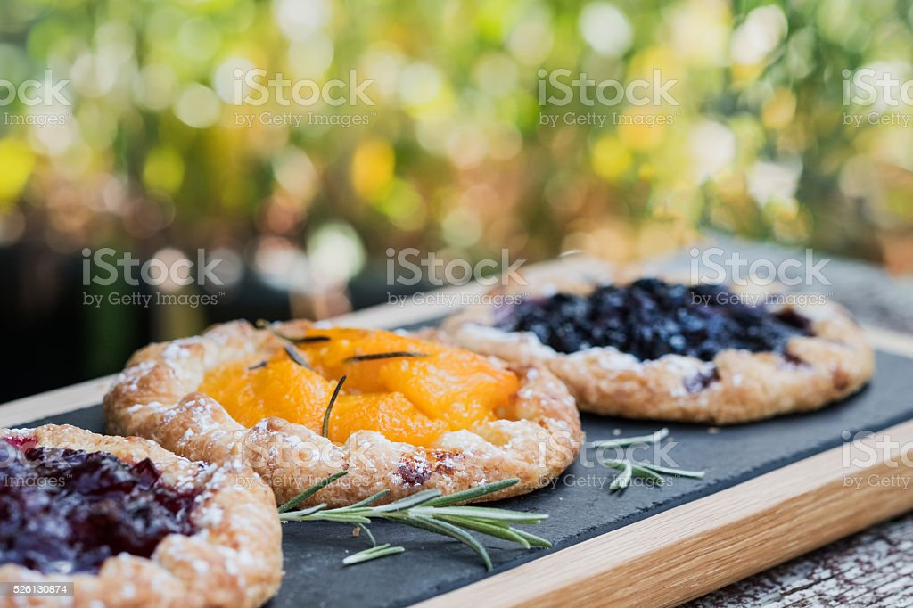 Rustic Handmade Fruit and Berry Tarts on Garden Patio Table stock photo