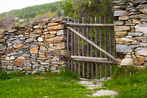 Rustic handmade wooden gate in a stone wall stock photo