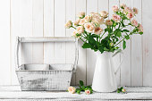 Rustic home decoration: light pink roses bouquet in jug and box against white rustic wooden wall.