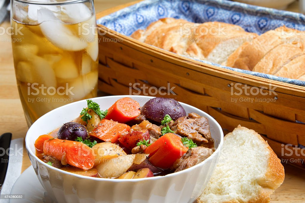 Rustic Homemade Artisan Beef Stew, bread and iced beverage stock photo