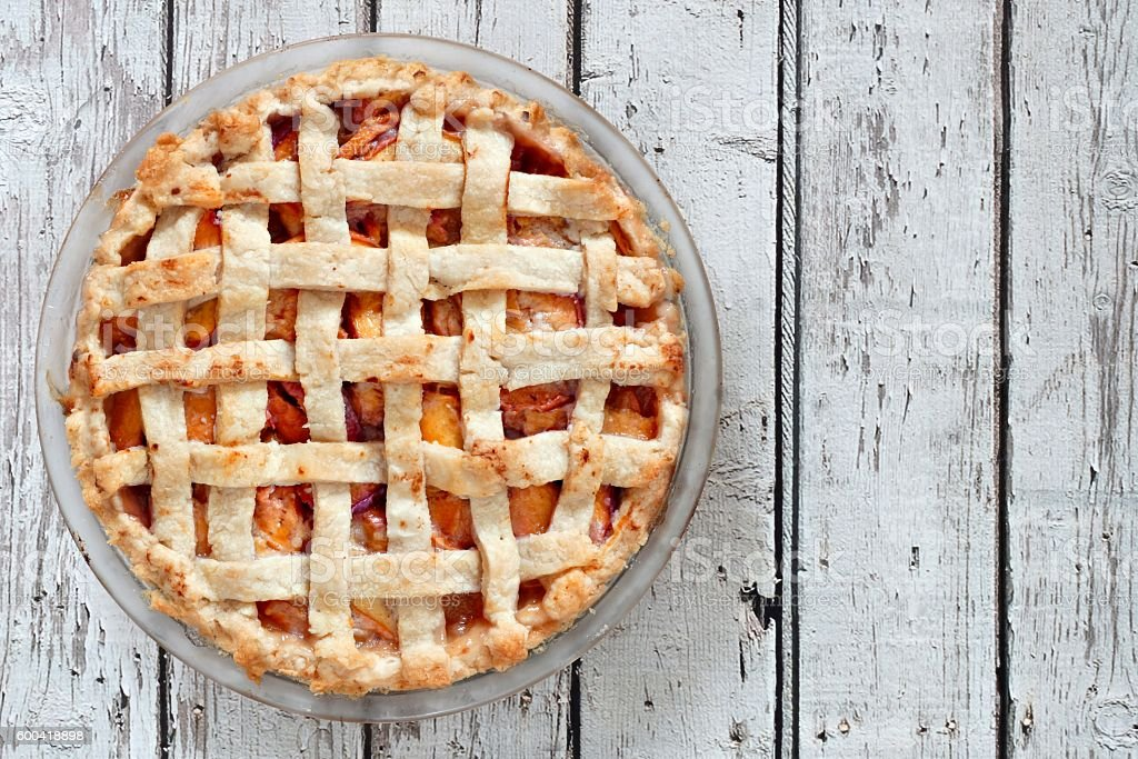 Rustic homemade peach pie, above view on aged white wood stock photo