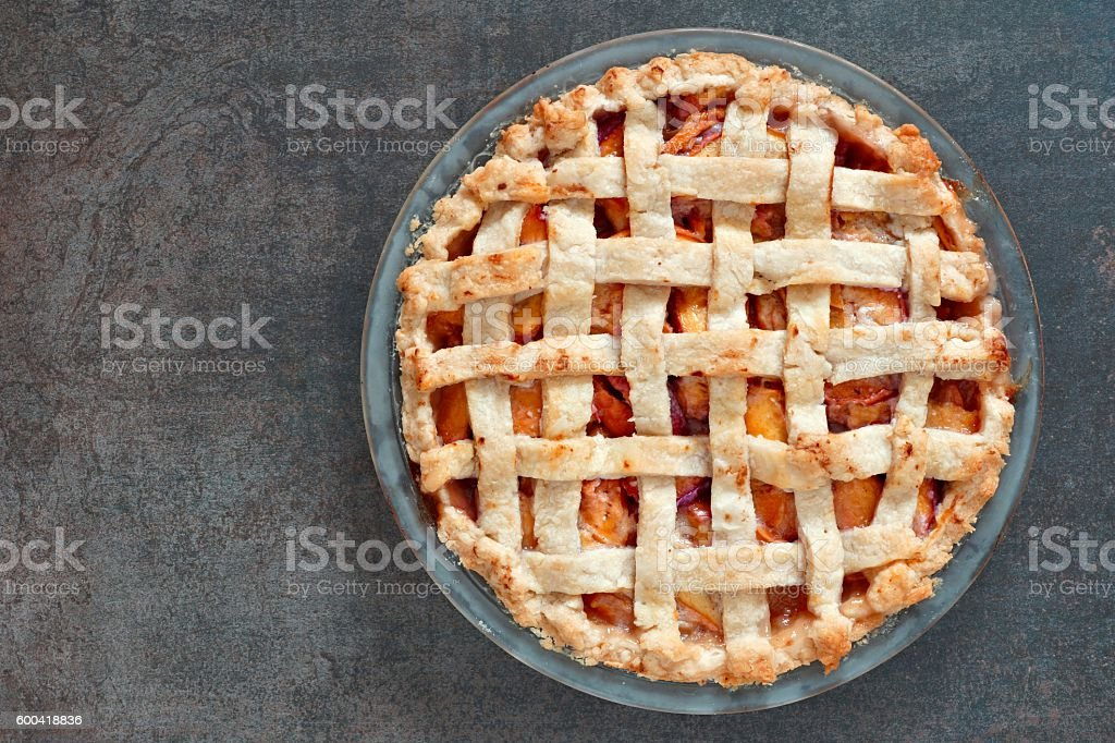 Rustic homemade peach pie, above view on stone background stock photo